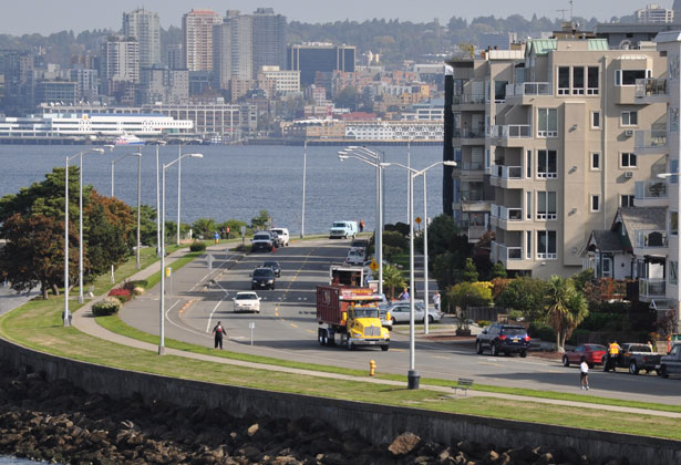 image of hungry buzzard truck driving on seattle waterfront with dumpster in back